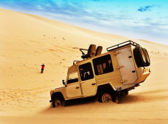 Namibia, Off-road vehicle driving down sand dune